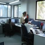 3 pessoas em escritório com mesas e computadores